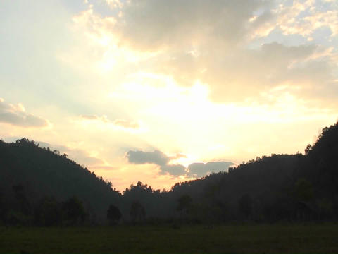 The sun rises over mountains and a body of water Footage