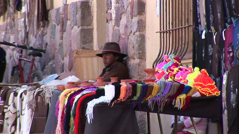 A latin American man sits at a souvenir stall selling... Stock Video Footage