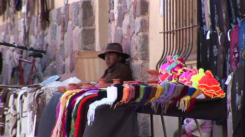 A latin American man sits at a souvenir stall selling goods along a street in South America Footage