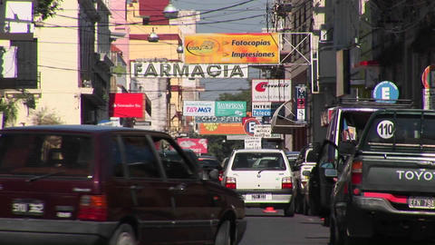 Argentina town with cars and businesses with signs in Spanish close up Footage