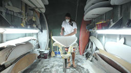 Surfboard shaping, Shaper using blower to blow the foam of the surfboard blank Footage