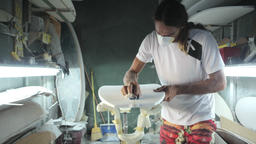 Surfboard making, Shaper is shaving and cleaning a line on a surfboard Footage