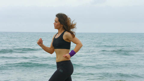 Serious young woman with concentrated face expression running along sea beach Footage