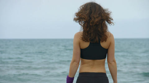 Pretty female sportswoman stops to enjoy beautiful seascape view, looking at sea Footage