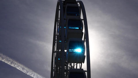 Sun light shine through glass of ferris wheel cabins, large construction move Footage