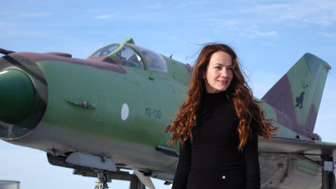 Young woman stand against MiG-21 Fishbed supersonic jet fighter aircraft Footage
