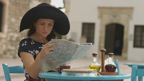Pretty female tourist sitting in cafe with map in hands, examining journey route Footage