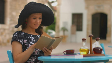 Pretty woman reading old paper book in cafe, enjoying rest, relaxing on vacation Footage