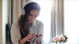 Woman listening music in headphones in room Archivo