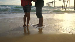 Passionate couple holding each other on the beach at sunset Archivo