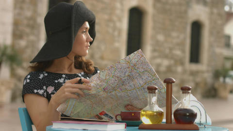 Young woman traveling abroad, planning trip with map in hands, searching sights Footage