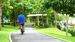a young man riding a bicycle in a park Footage