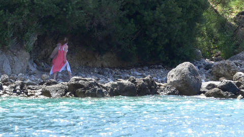 Woman in pink dress walking on the rocky beach of stormy sea 22a Footage