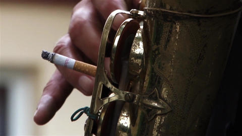 Fingers of a musician who press the keys of a saxophone while consuming only cig Live Action
