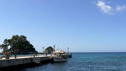 Panorama with boat stopped at the pier in sunny summer day and a man sits on a b Footage