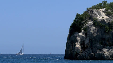 Sailing boat bound for ocean bypassing the a cliff full of vegetation that grew  Footage