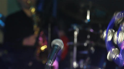 Spotlights shining while the band plays on the stage next to a microphone placed Footage