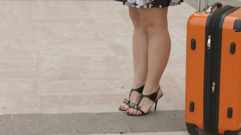 Woman with beautiful legs in high heel shoes waiting for train, bus at station Footage