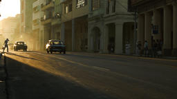 Pedestrians and classic cars during the sunset glow in Havana Footage