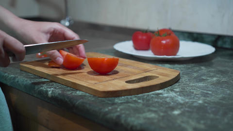 Extreme close-up of female Caucasian hands cutting tomato with kitchen knife Live Action