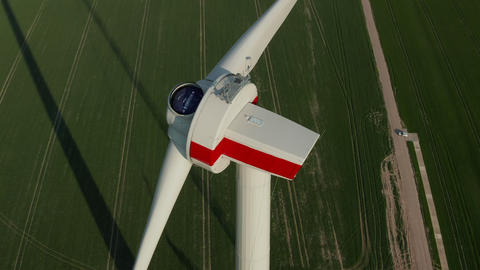AERIAL: Close up of Wind Turbine under construction being build on rich green Live Action