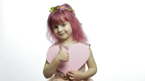 Child girl princess holds pink paper heart. Mothers day, Valentines day concept Live Action