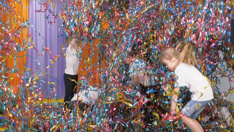 Colored ribbons fly in different directions. Bright children's emotions. Children jump holding foil Live Action