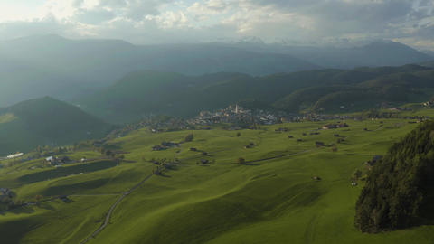 Aerial view of improbable green meadows of Italian Alps, green slopes of the Live Action