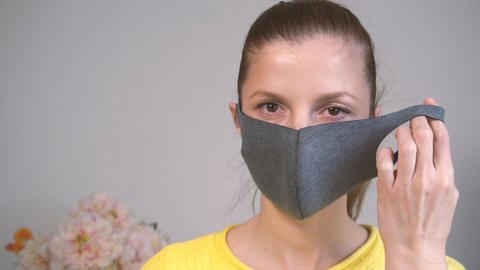 Woman looking in camera and taking off face protective mask Live Action