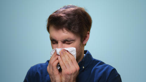 Sick man sneezing in studio. Ill man using napkin on blue background Live Action