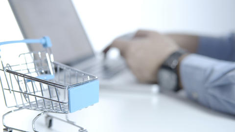 Cart on white desk and blurry a man using laptop for shopping online with credit card Live Action
