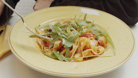 Delicious gourmet pasta with Eruca vesicaria at a restaurant Live Action