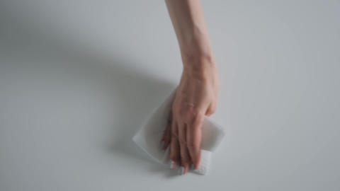 Disinfection concept - woman cleaning white table with wet wipe - slow motion Live Action