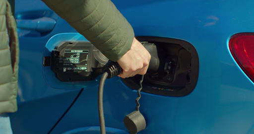 Man plugging in hybrid car at home at electro charging station. Luxury blue Live Action