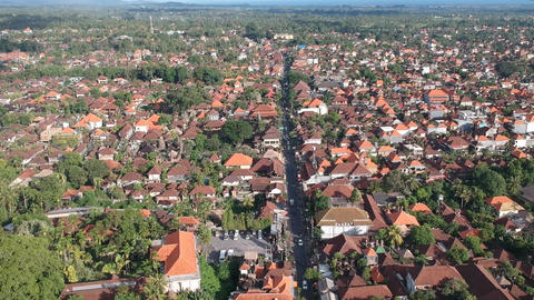 drone flying over the center of ubud jl.Raya Ubud in sunny weather, houses with Live Action