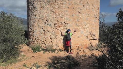 Woman gives hug defense tower torre de Cap Andritxol, Mallorca, Spain. Trail along west shore of Live Action