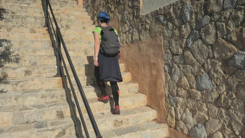 Sea shore architecture. Woman climbing up by thin stairs from sea side to old town of Camp de Mar. Live Action