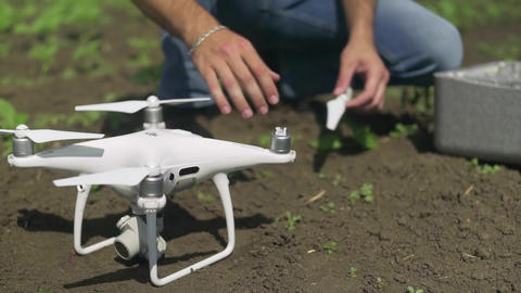 Drone pilot instal propeller on his white drone outdoors Live Action