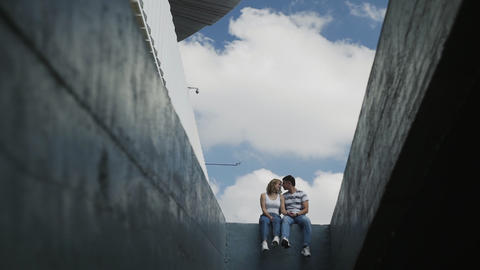 Young Attractive Couple in blue jeans sits on concrete wall Live Action