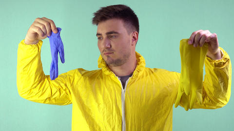 A sad cleaner in a yellow suit makes a choice between a blue and a yellow glove Live Action
