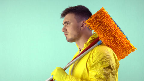 A cleaner in a yellow suit and yellow gloves, holds a broom and a mop in his Live Action