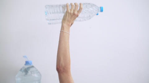 Sport at home. Workout at home. Man doing exercises using plastic water bottles Live Action