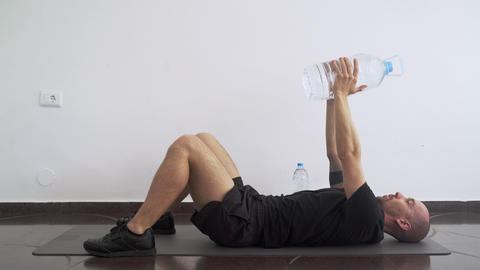 Sport at home. Workout at home. Man doing exercises using plastic bottle of Live Action