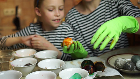 Easter family togetherness. Mother and daughter in striped dress decorate Easter eggs together at Live Action