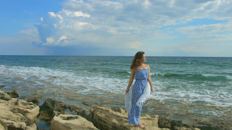 Happy beautiful woman standing on rocky sea beach, foamy waves crashing ashore Footage