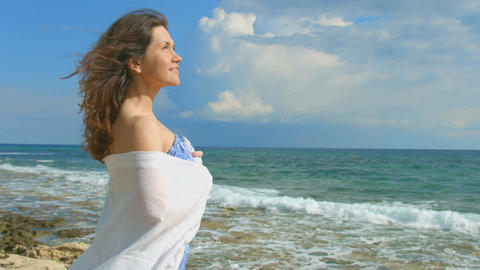 Pretty woman dreaming on the beach, beautiful ocean waves coming ashore, nature Footage