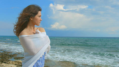 Lonely brunette wrapping herself in scarf, looking at ocean waves. Windy weather Footage