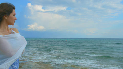 Horizontal panorama of beautiful lonely woman on sea shore, hair waving in wind Footage