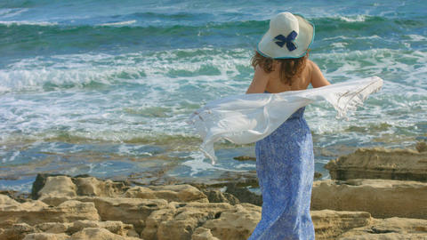 Young elegant woman holding scarf in wind, ocean waves crashing on rocky beach Footage