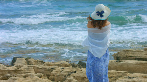 Lonely female wrapped in scarf watching foamy ocean waves crash on rocky beach Live Action